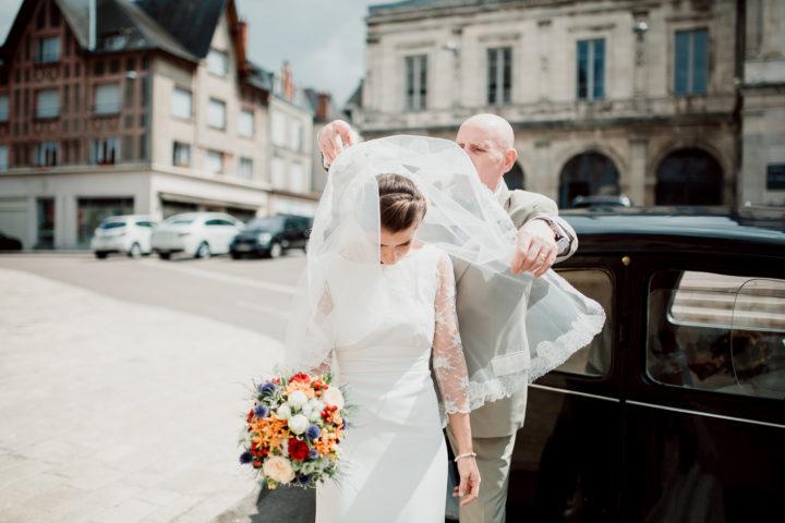 Le père de la mariée lui met son voile