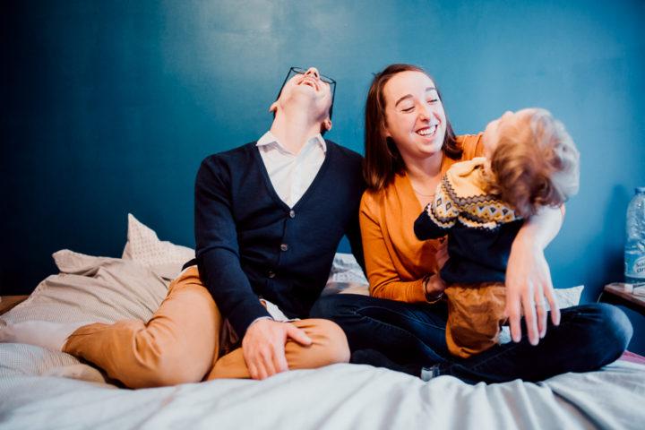 La famille rigole sur le lit parental