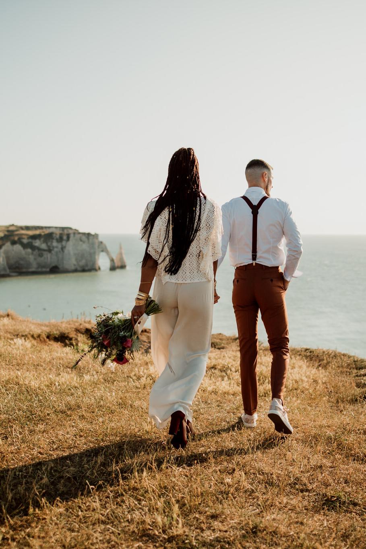 Jeune couple de mariés marchant sur les falaises d'Etretat