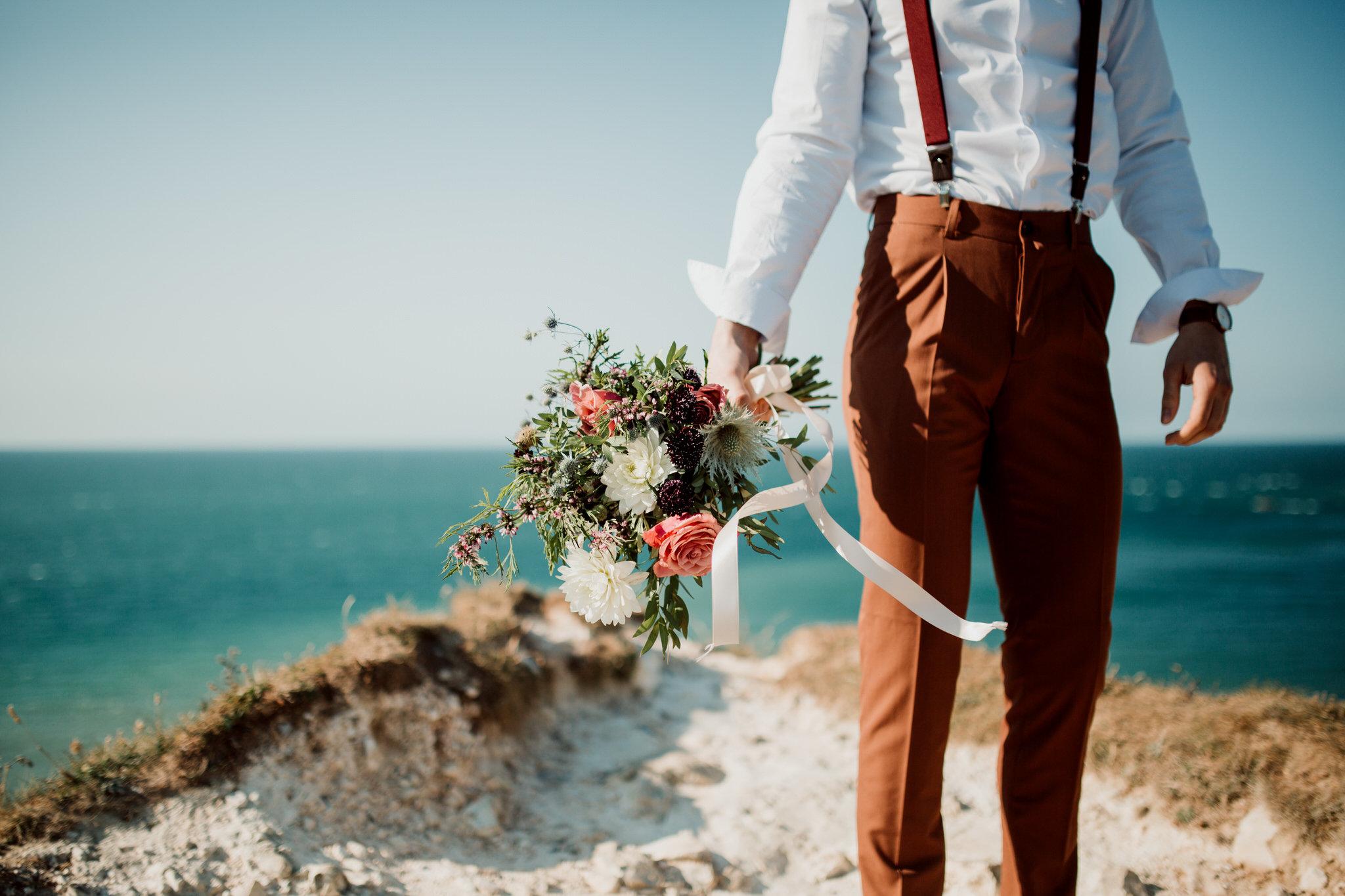 Bouquet de fleur de mariage tenu par le marié à Etretat